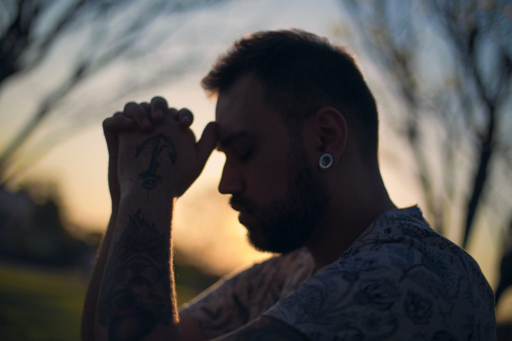 man prays working on sobriety from ibogaine treatment for heroin addiction